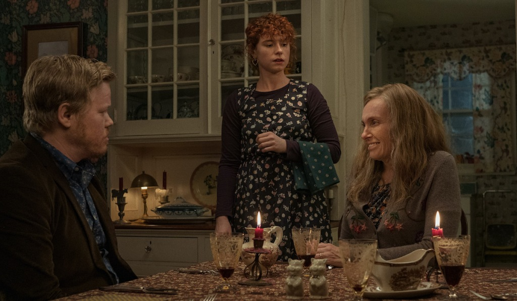 A young woman (Jessie Buckley) stands over her unimpressed boyfriend (Jesse Plemons) and his bemused mother (Toni Collette) who are sat at a dinner table. From 'I'm Thinking of Ending Things'.