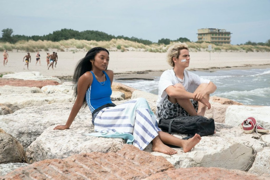 The two man characters, Fraser and Caitlin, sit together on rocks by the ocean