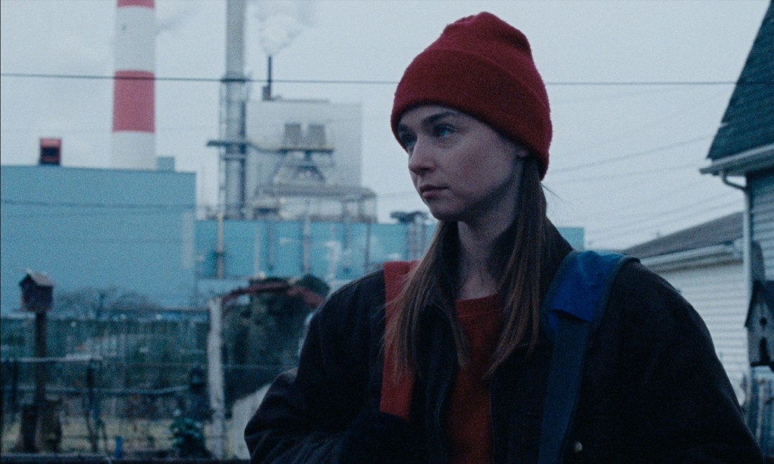 Image shows Ruth (Jessy Barden) standing in front of an industrial plant.