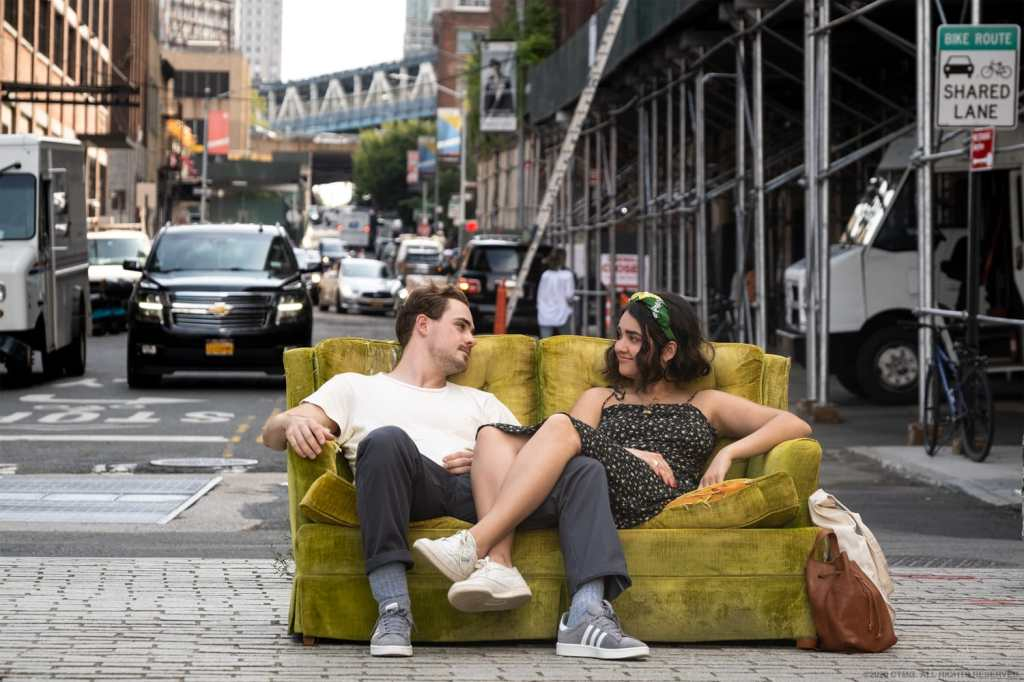 "Geraldine Viswanathan and Dacre Montgomery in a still for ""The Broken Hearts Gallery"". They are sitting on a green couch in the middle of the street."