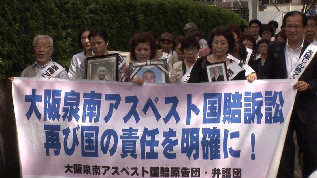 Image shows a protest march for the victims of asbestos related illnesses in Sennan, Japan, with family members holding banners and pictures of loved ones.