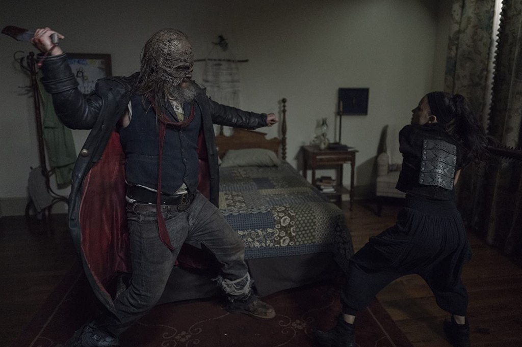 Image still from The Walking Dead episode Stalker. Beta towers over Rosita in a bedroom as they fight to the death.