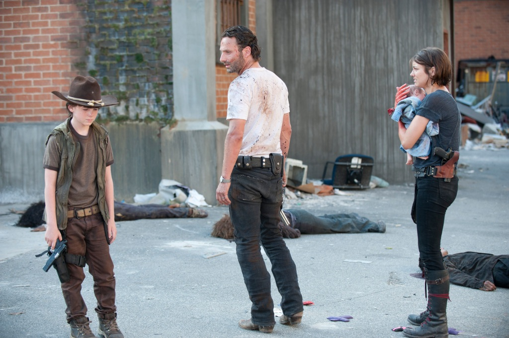 Image still from The Walking Dead episode Killer Within, a bloodied Carl, Rick, and Maggie carrying baby Judith, all look distraught.