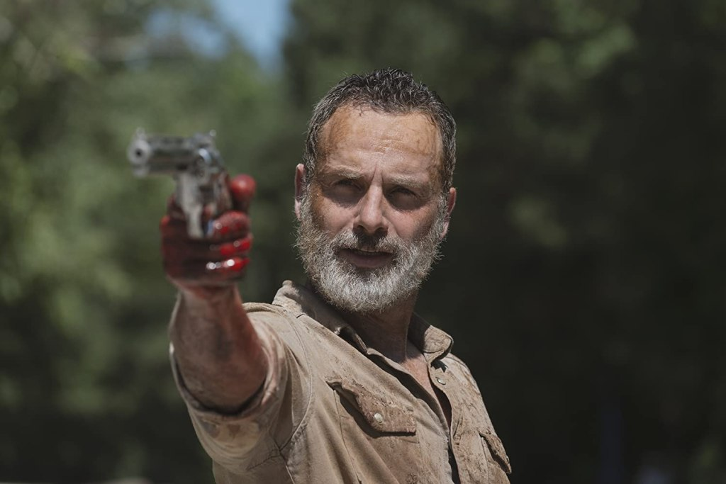Image still from The Walking Dead episode What Comes After. A dishevelled Rick looks into the camera, bloodied hand and pointing his gun.