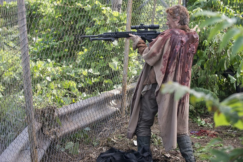 Image still from The Walking Dead episode No Sanctuary. Dressed in a bloodstained cloak, Carol aims a sniper rifle through a steel fence.