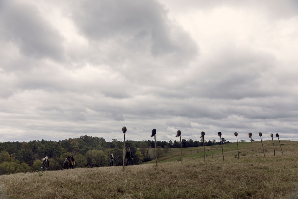 Image still from The Walking Dead episode The Calm Before. Overcast sky, impaled into the ground is a row of severed heads blowing in the wind.