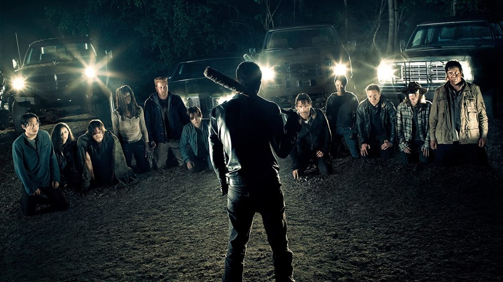Image still from The Walking Dead episode The Day Will Be When You Won't Be. A night-time shot of Negan standing menciangly in front of all the major cast as they kneel submissively before him.