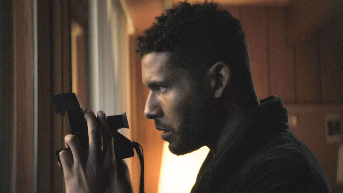 Image from the film Spiral. A man looks through a door holding a camera.