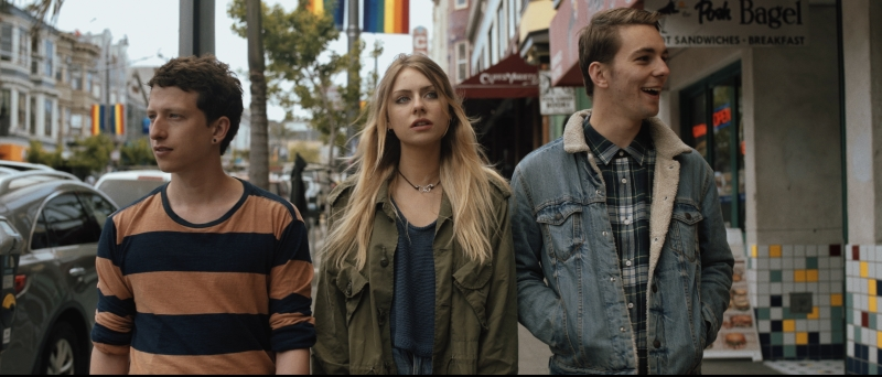 three young adults walk outside in San Francisco, with rainbow pride flags on the lampposts