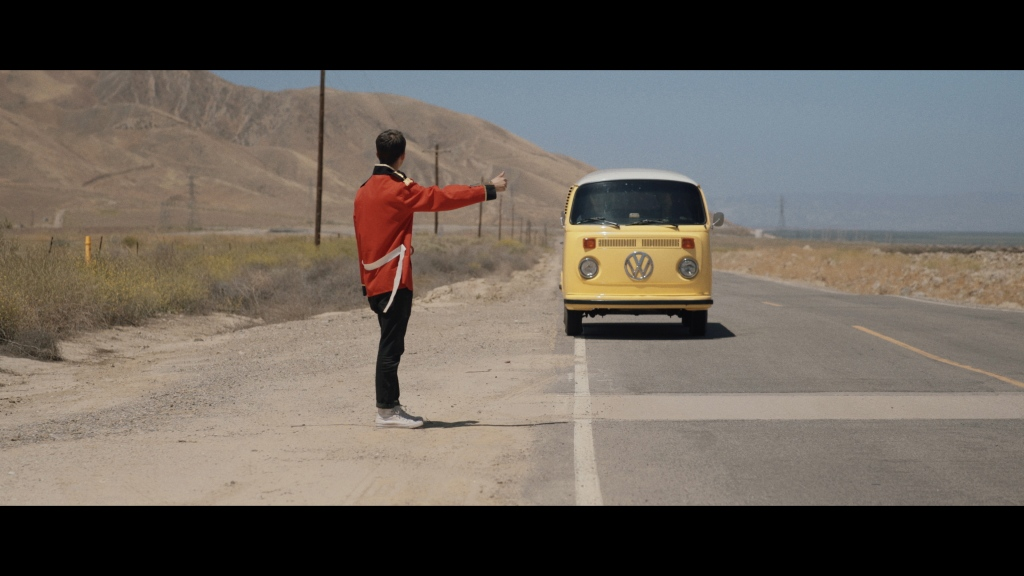 A man in a red coat attempts to hitch a ride from a yellow campervan.