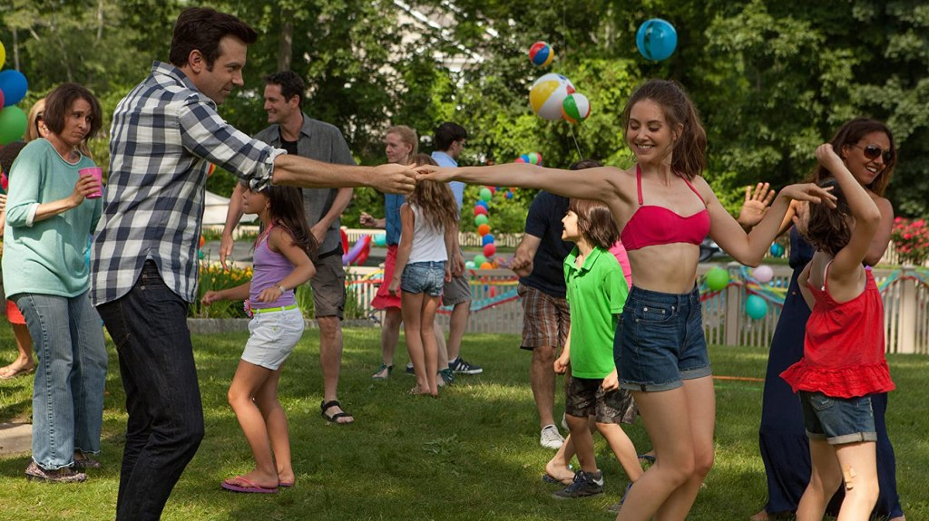 Jake and Lainey hold hands while dancing at a child's birthday party.