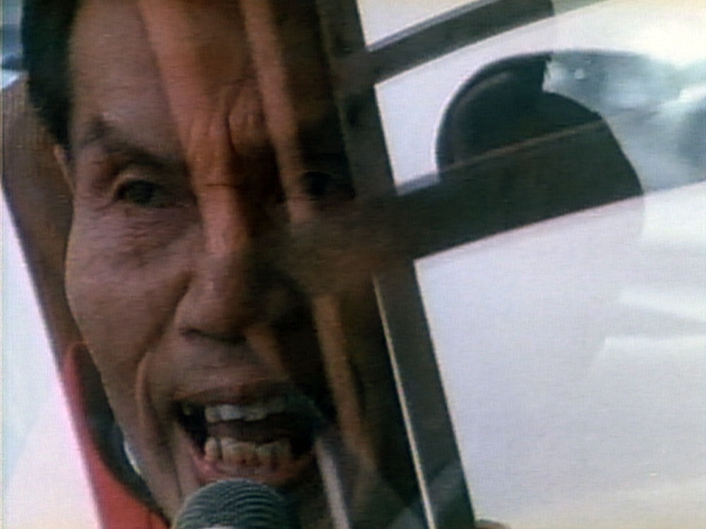 Image from the film The Emperor's Naked Army Marches On. A man peers out of a window holding a microphone.