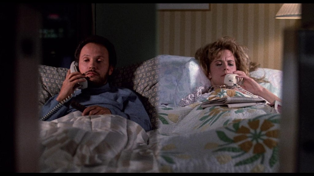 Harry and Sally pictured on a split screen talking on the phone in bed.