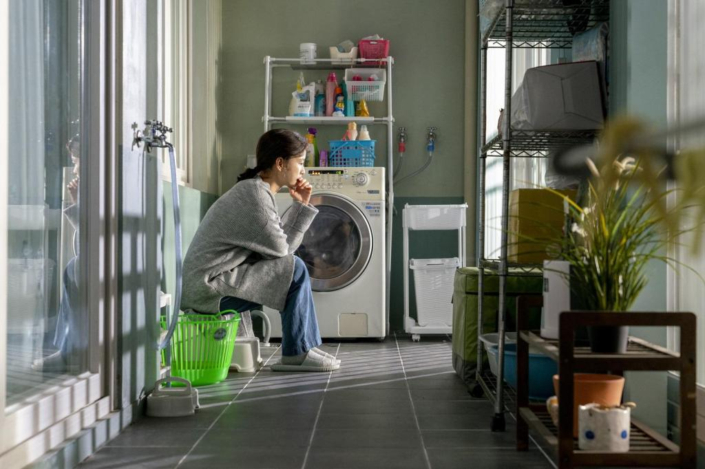 Ji-young (Jung Yumi) sits in her laundry room and looks pensive.