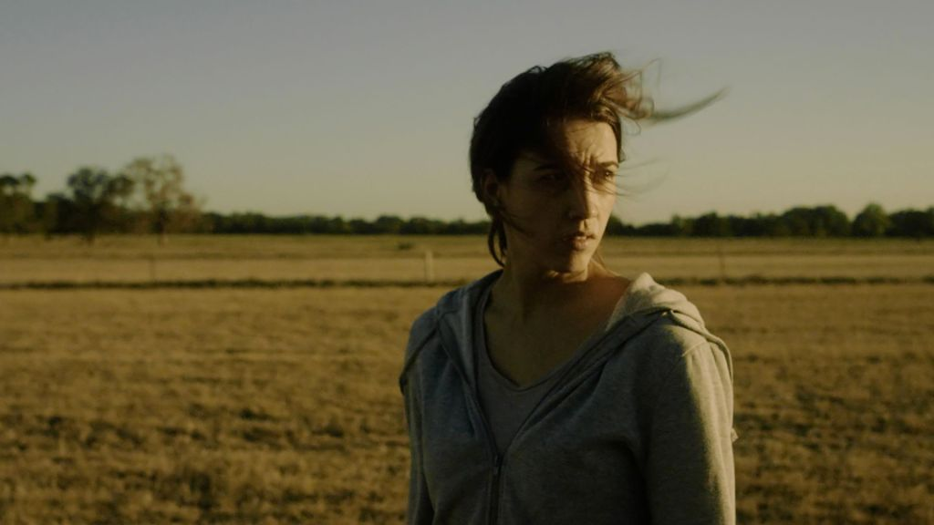 A woman looks distressed and confused in a field. She is wearing a hoodie and t-shirt and her hair blows to the right in the wind.