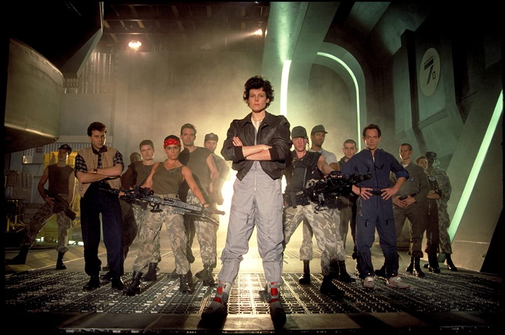 Ripley stands center with her entire spaceship crew of 14 stands in a line behind her