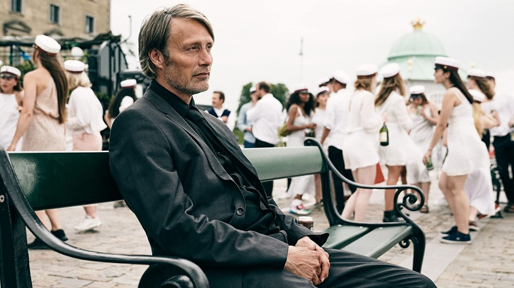 Martin (Mads Mikkelsen), in a dark suit, sits on a bench whilst students in white graduation outfits mingle behind him. From 'Another Round'