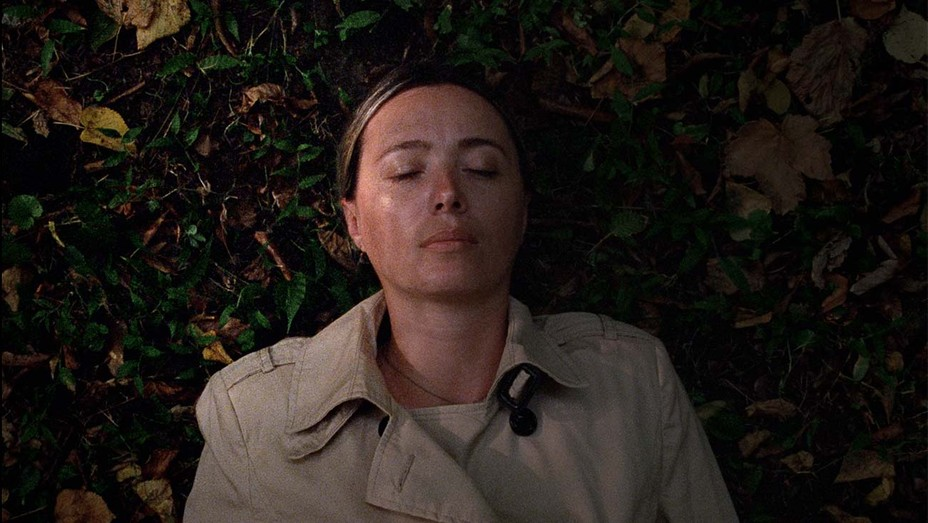 This image is from the film Beginning. A woman lies on the ground with her eyes closed.