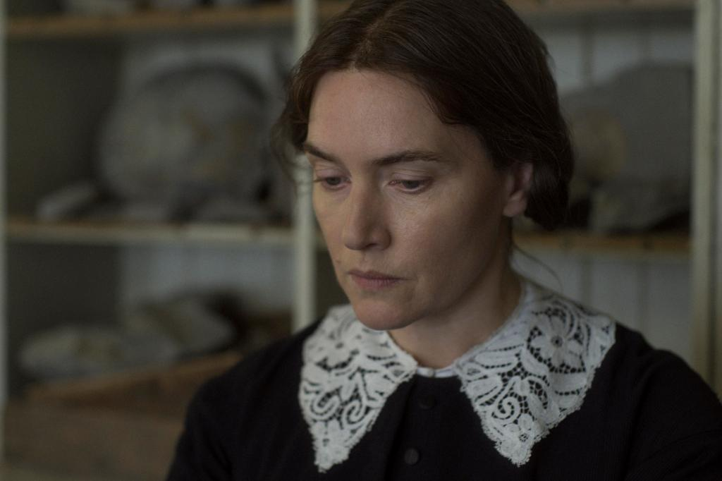 Kate Winslet, playing the part of Mary, stands in her kitchen with a black dress and white lace collar. She looks upset, her face unmoving