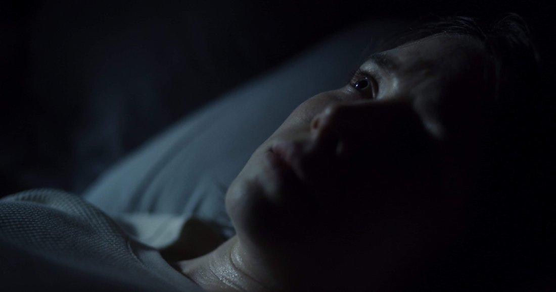 Rowan lays awake in bed.