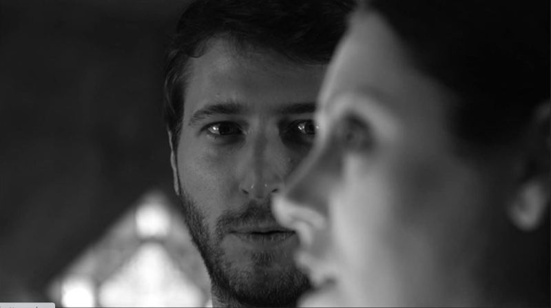 Image from the film 'A Ghost Waits'. A man looks lovingly at a woman, who is out of focus in the frame. The image is in black and white.