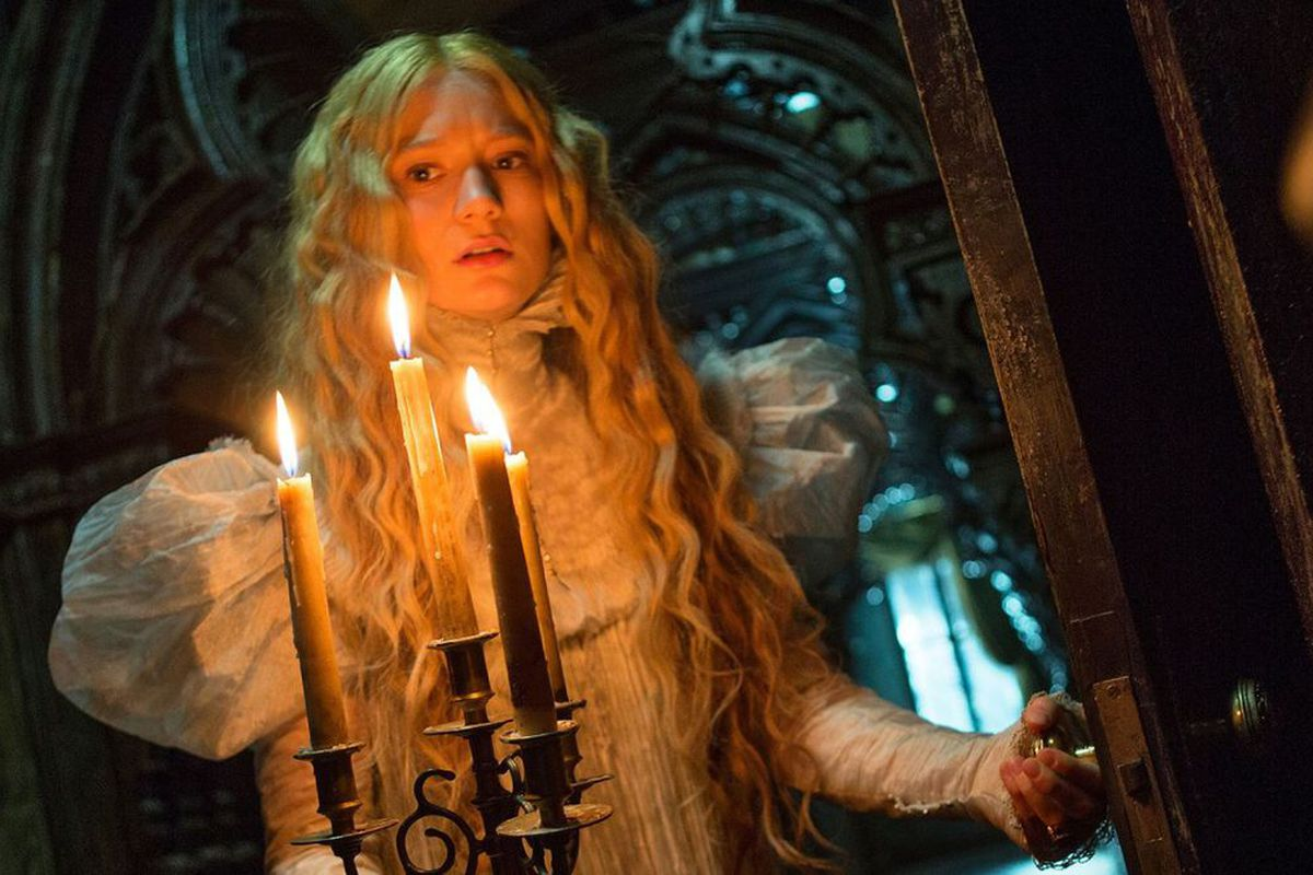 A pale woman with long wavy hair in a white Victorian dress carries 4 lit candles in a dark hallway