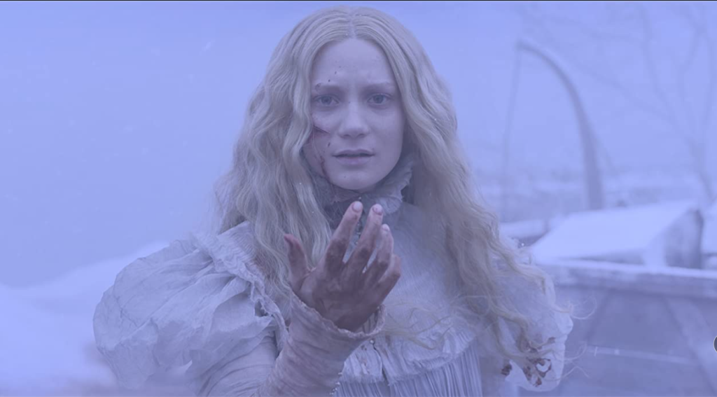 A pale woman in a white Victorian dress with long blonde hair stands outside in a blizzard, holding her blood spattered hand in front of her face with large cuts