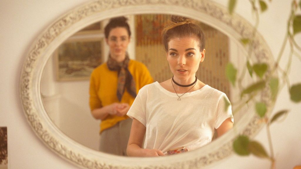 "Two women can be seen reflected in an ornate mirror, with one of them being out of focus. The room surrounding them has a ""hipster"" vibe."