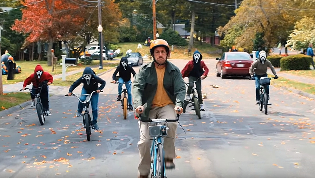 Adam Sandler as Hubie rides a bicycle as he is being chased by a group of children wearing Ghostface masks.