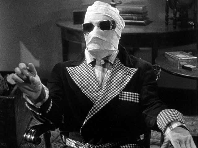 Claude Rains as The Invisible Man, wrapped in bandages and sitting down.