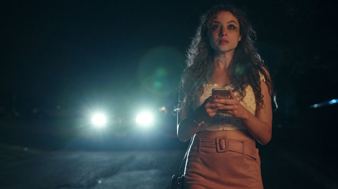 A woman stands looking past the camera. She is dressed for a party and holds a phone in her hand. A car's headlights can be seen in the background, approaching her.