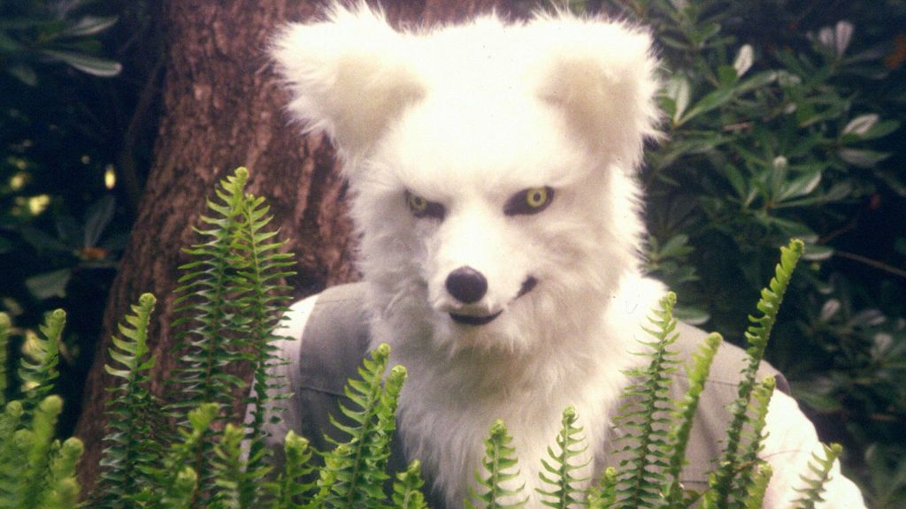 A person in a white fox mask peers from behind a collection of plants. Behind the person is a tree and more greenery.