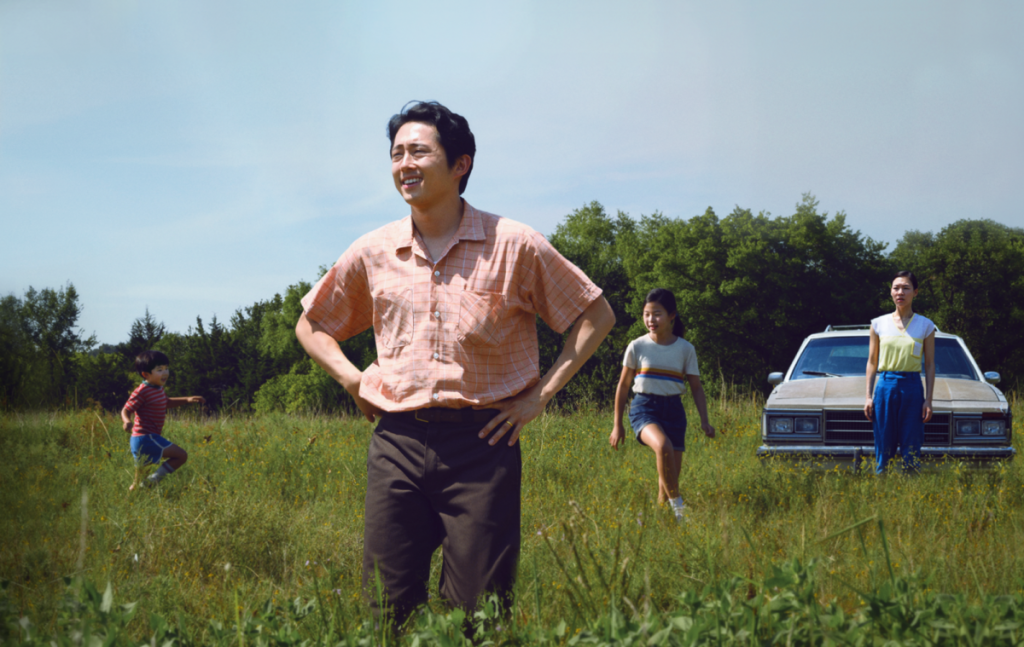 In a grass field, a man stands with his hands on his hips. Around him, two children play and a woman stands by a car, looking out into the distance.