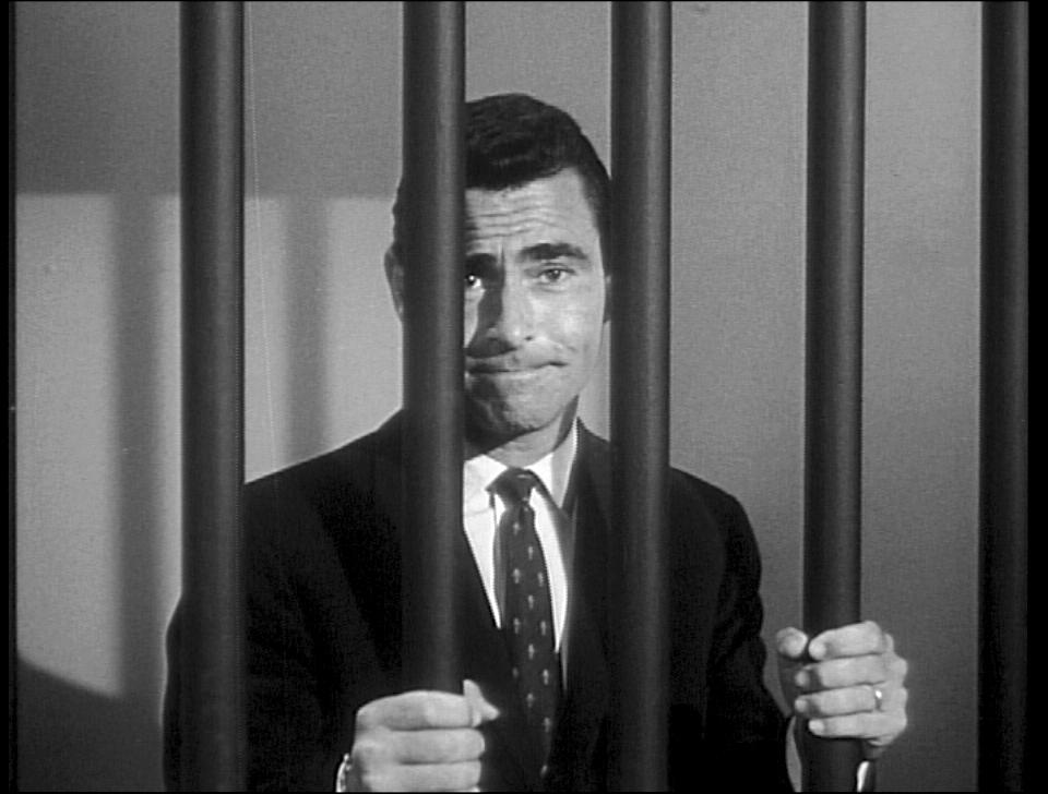Rod Serling standing behind bars