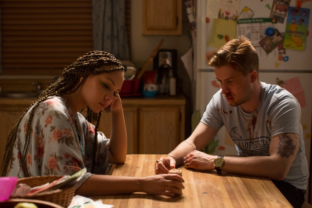 Miles and his partner Ashley (Jasmine Cephas-Jones) sitting at the kitchen table, looking upset.