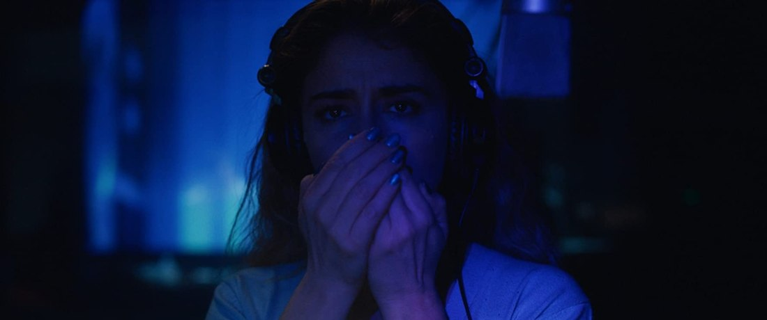 Image still from the horror film The Intruder. A dark, blue-tinted background, a woman (Érica Rivas) dubs sound effects into a microphone.