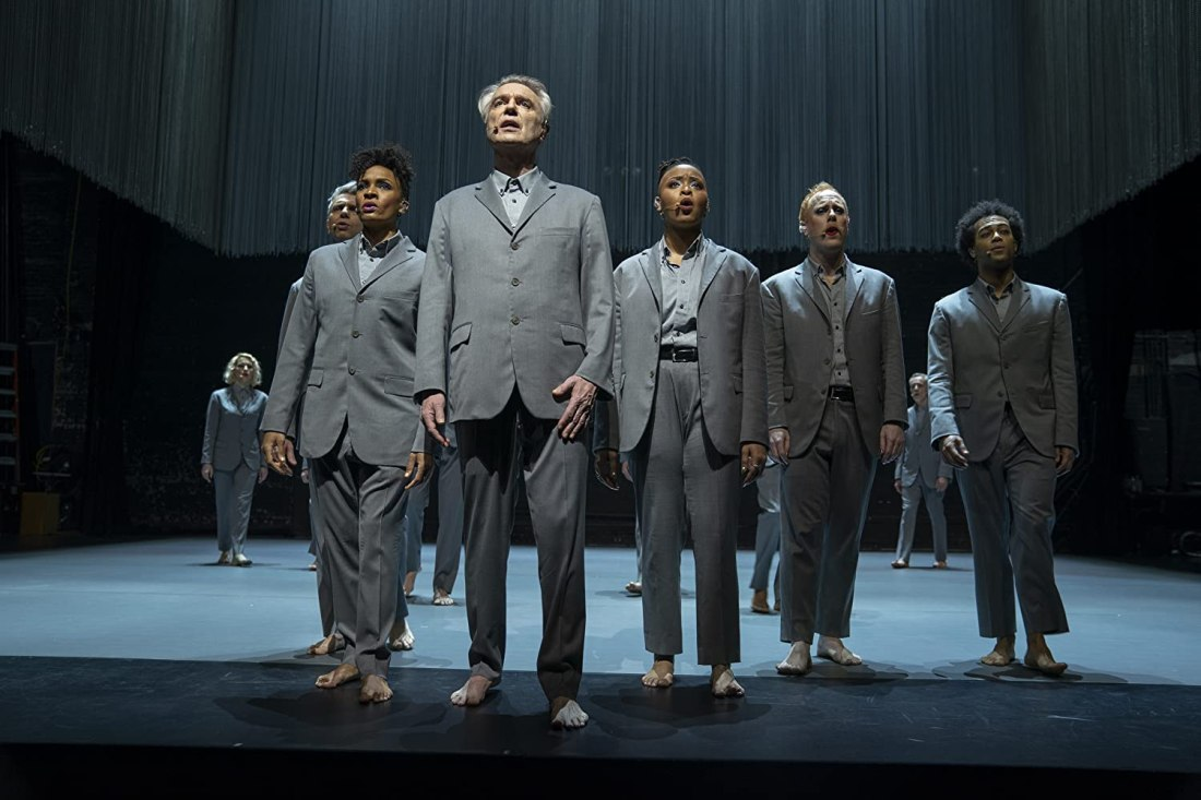 David Byrne and others stand and sing together on stage.