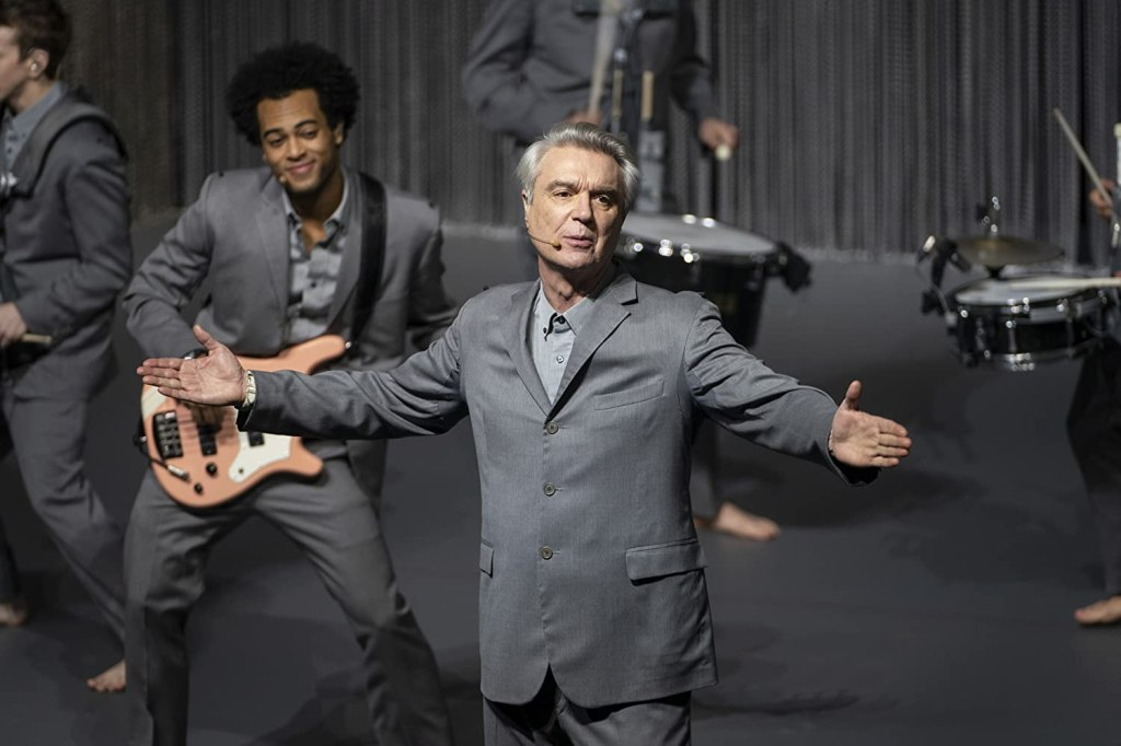 David Byrne sings on stage whilst a musician smiles behind.