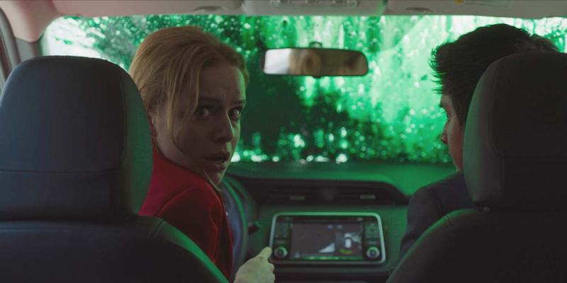 Image still from the film New Order. A woman and man sit in the front seats of a car that's had its window shield splashed with green paint. The woman looks behind horrified.