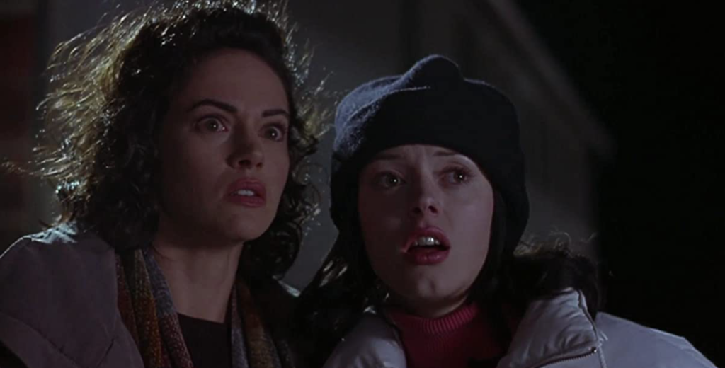 two women in coats and hats look to the side of the camera with fear in their eyes