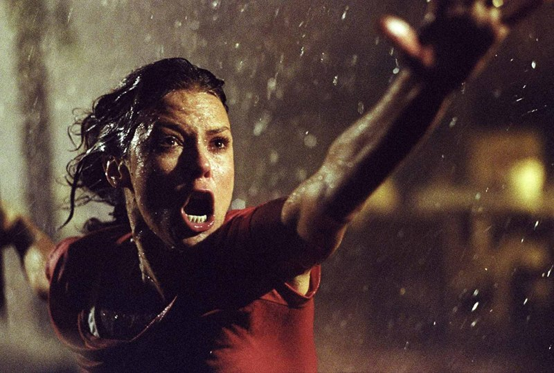 a woman reaches one arm toward the camera with her mouth agape in the rain