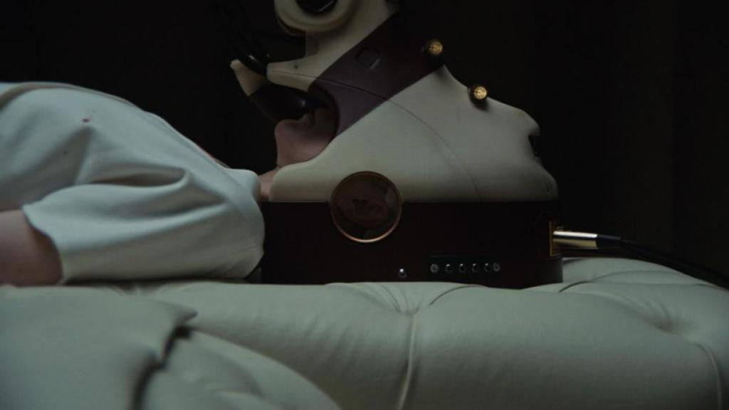 A woman in a white medical top (Andrea Riseborough) lies on a cream sofa wearing a futuristic headset. From 'Possessor'