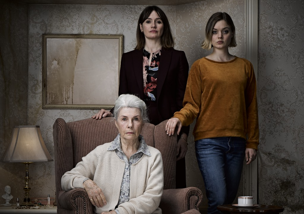 Image from the horror film Relic. Three women pose for a family portrait in a decrepit looking living room, staring into the camera.