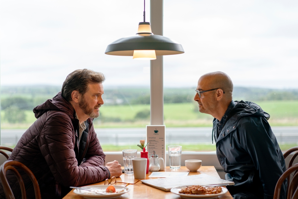 Sam, Colin Firth, and Tusker, Stanley Tucci, sit opposite each other in a British breakfast diner cafe