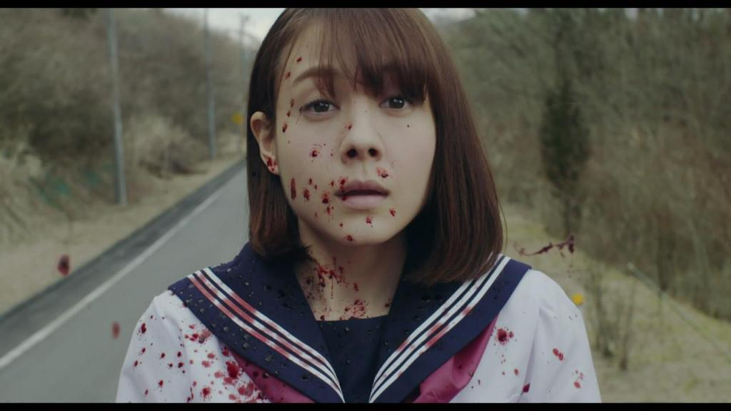 a teenage girl in a blood-splattered school uniform stands on an empty road