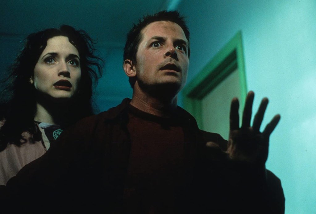 A man with his hand up and a woman standing to his back right face the camera looking scared