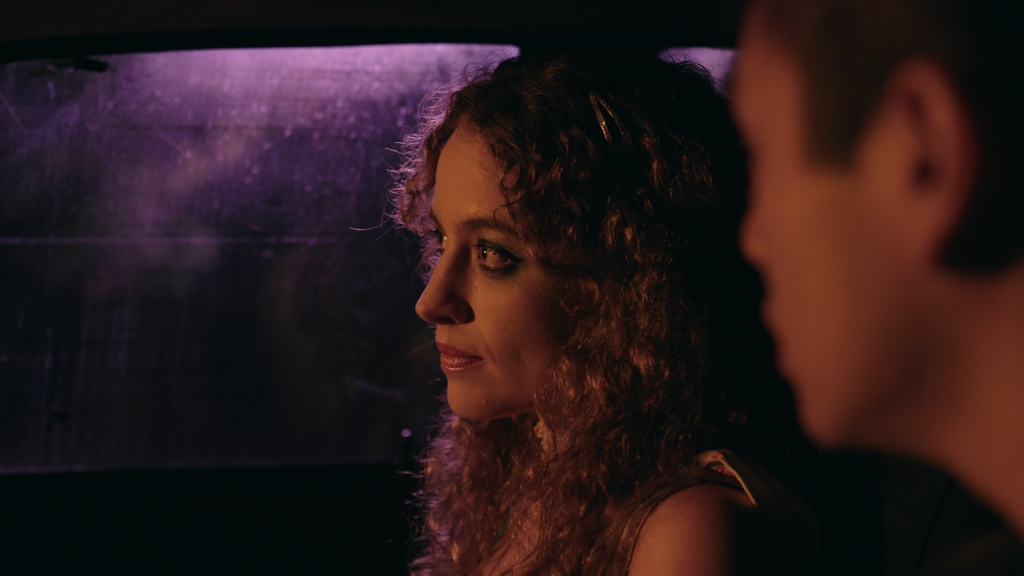 A woman and man sit in a car. The window is foggy, and the characters are lit by reddish purple lighting.