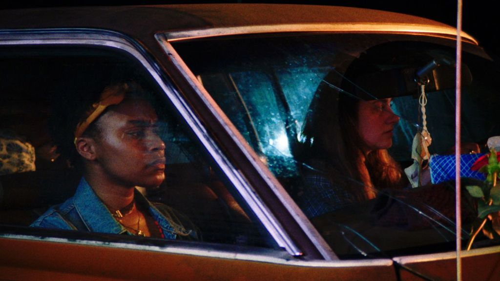 Two women sit in a car at night, looking out of the windshield.