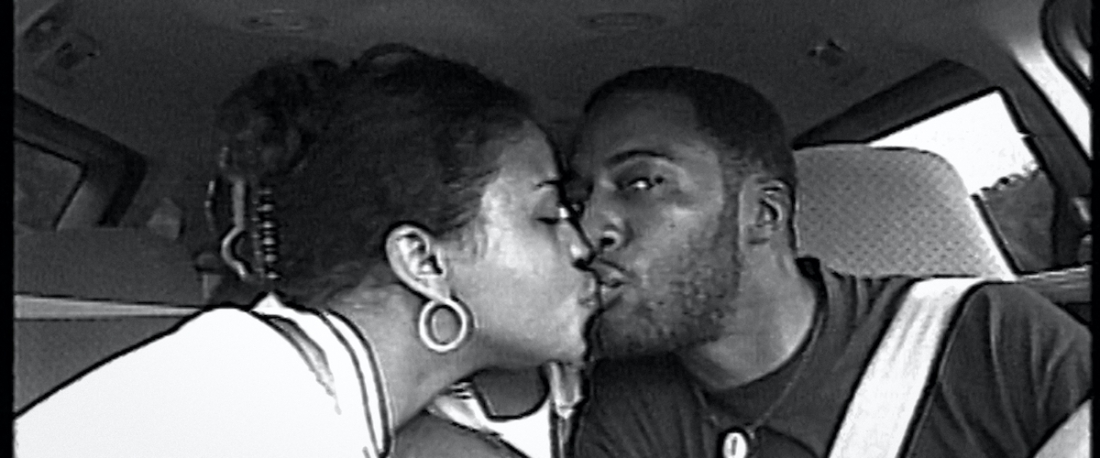 Image from the documentary Time (2020). It is a black and white image of a couple kissing in a car.
