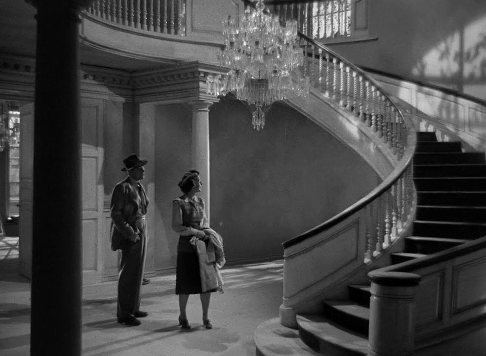 A black and white photo of a man and woman in semi-formal 1940s attire standing in the entry of a mansion with a large curved staircase and chandelier